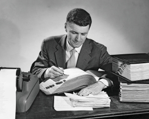 Businessman writing in an accounting ledger